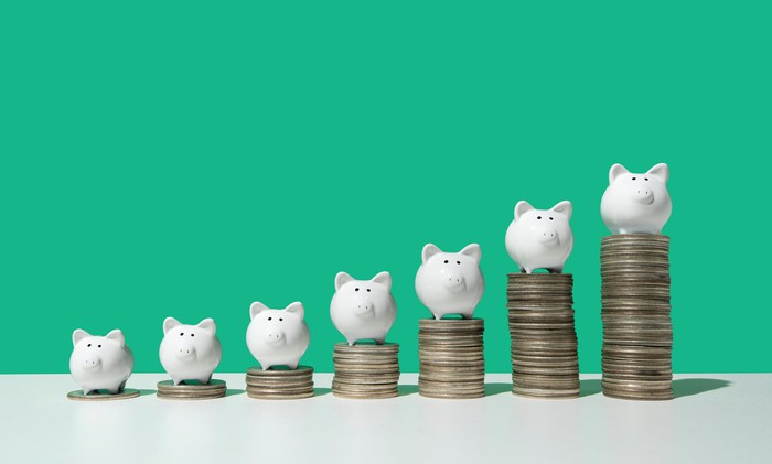 7 white piggy banks sitting on growing stacks of coins.