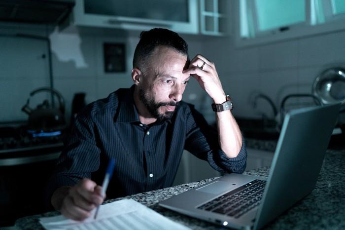 An person looks stressed sitting in the dark while looking at his computer screen.