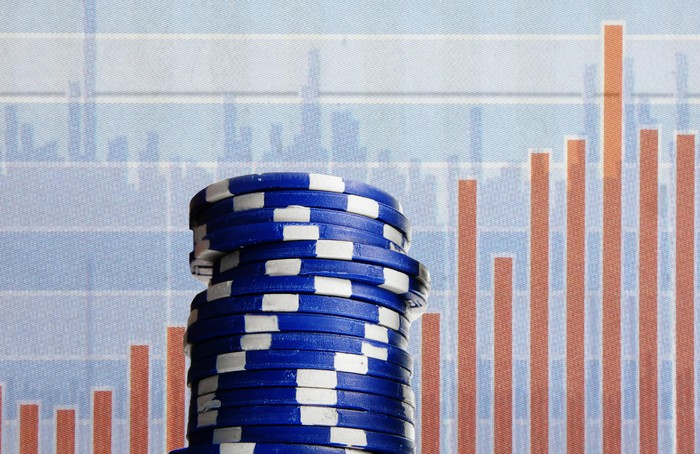 A pile of blue poker chips in front of two graphs.