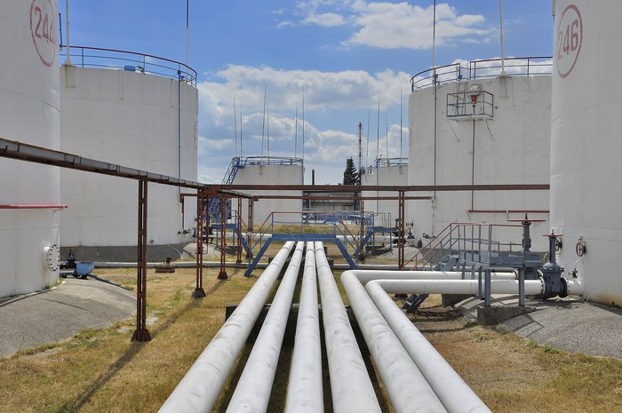 Multiple pipelines leading to crude oil storage tanks.