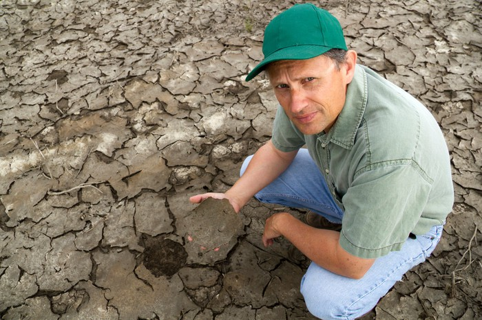 Farmer in a dry field holding up a large piece of cracked soil.
