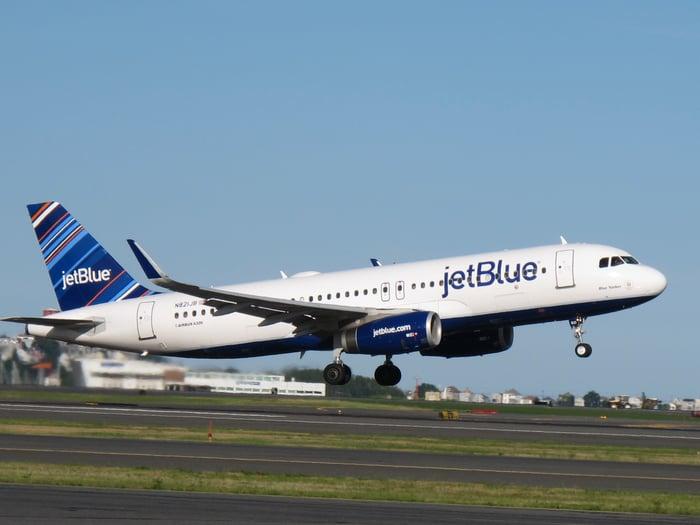 A JetBlue Airways plane preparing to land on a runway.