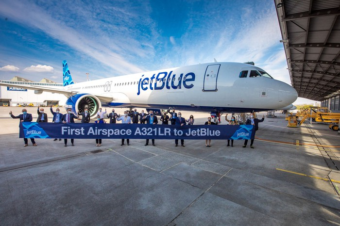People standing on the tarmac in front of a JetBlue plane celebrating the handover of JetBlue's first A321LR.