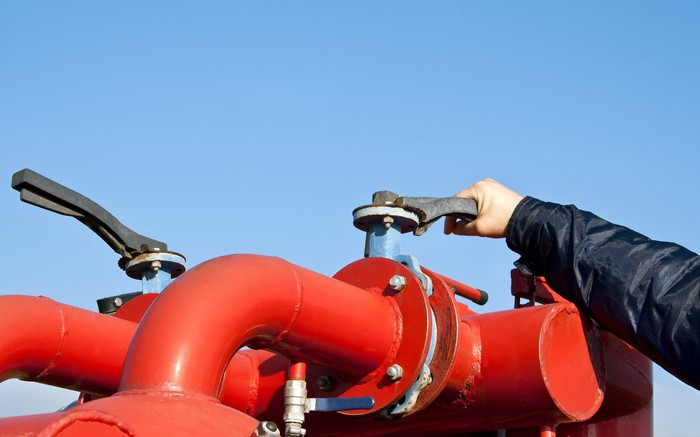A worker turns a valve on a red pipeline.