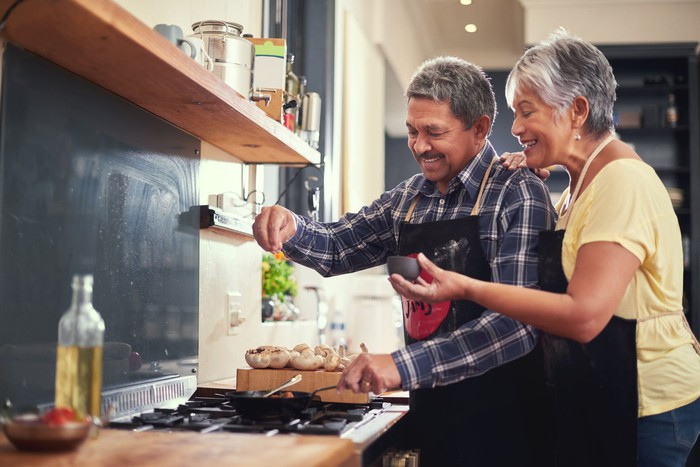 Older couple adding spices to food.