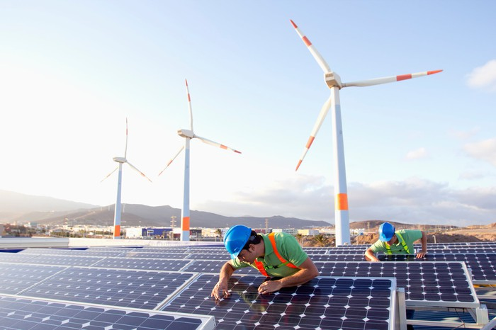 Workers inspecting solar panels with wind turbines in the background.