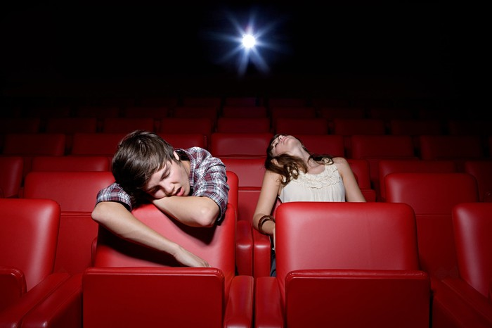 A pair of movie theater customers sleeping in an otherwise empty screen with the projector rolling.