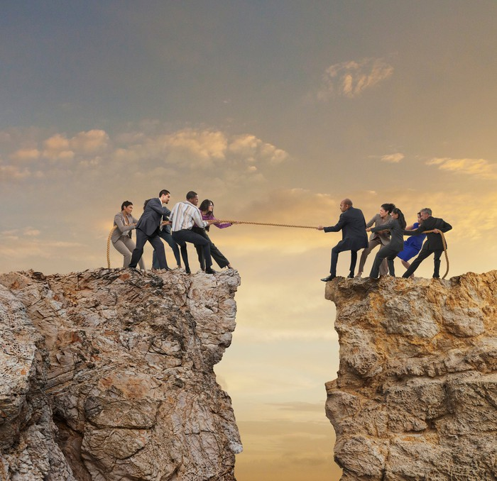 People having a tug of war over a chasm