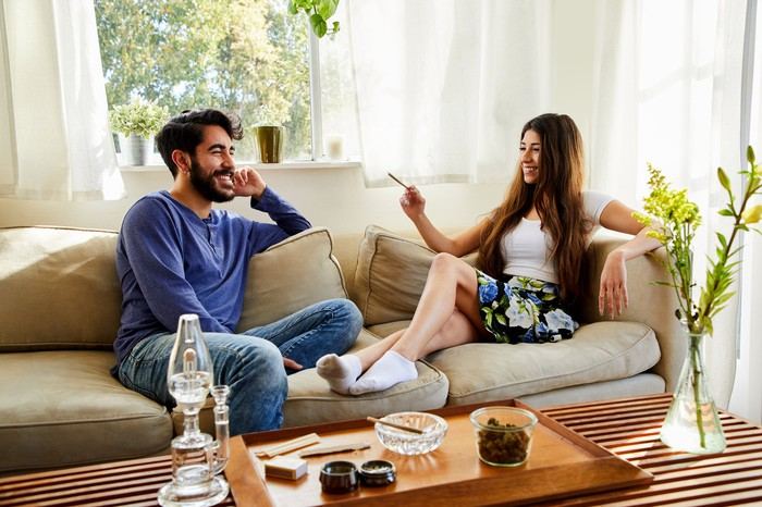 Two people on a couch in a room, with one holding a joint.