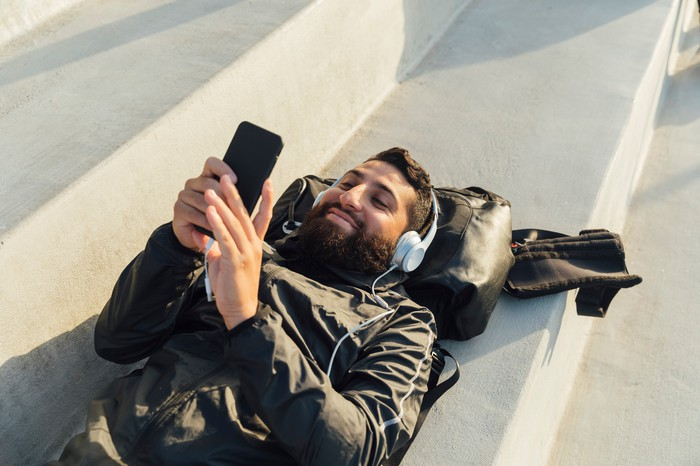 A person lying down outside listening to audio through headphones.