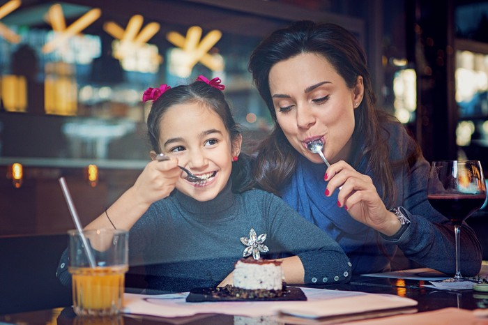 A parent and child sharing food in a restaurant.