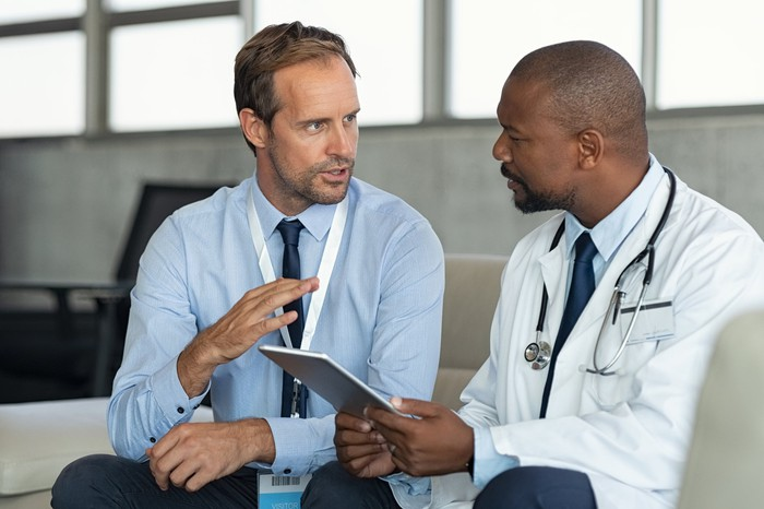 Pharmaceutical sales representative speaking with a doctor.