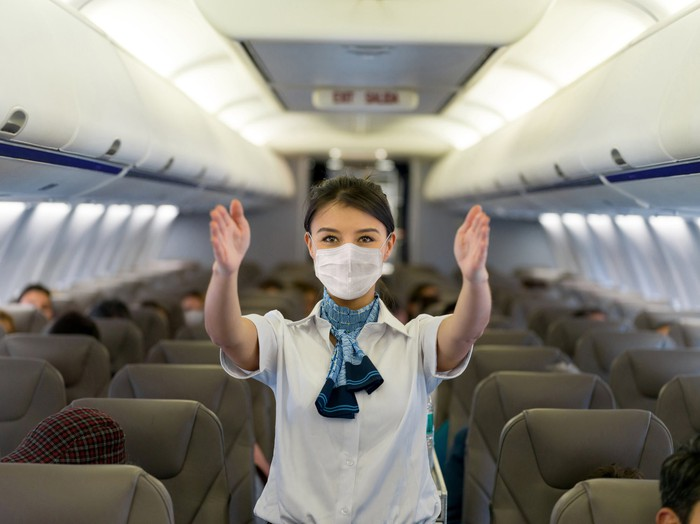 A flight attendant in a mask giving safety briefing on an airplane.