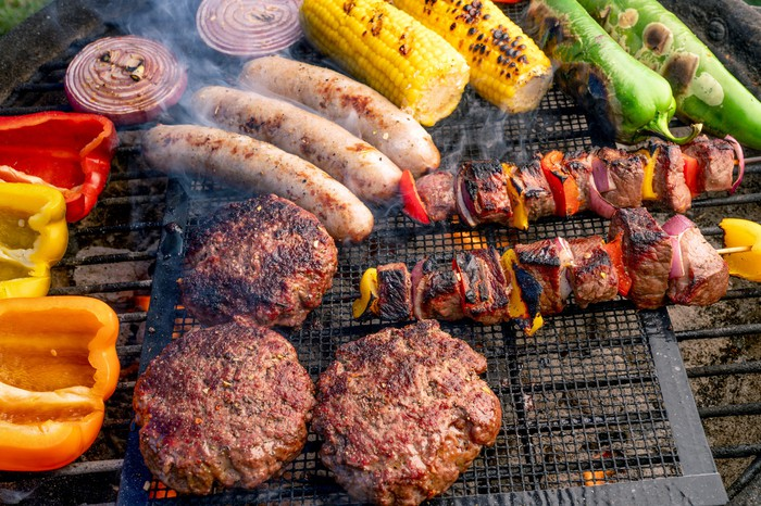 A charcoal grill cooking a colorful selection of meat and vegetables.