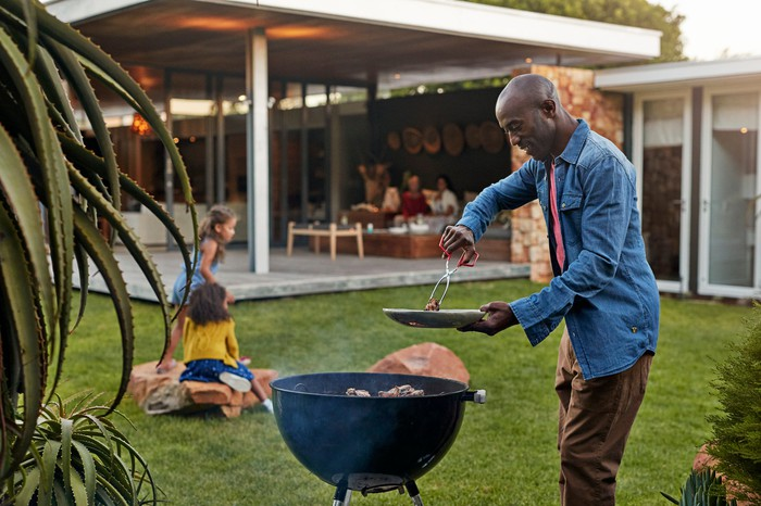 A person grilling in the backyard, while adults wait on the patio and children play in the background.