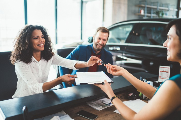 Person handing paperwork to two people at a car dealership.