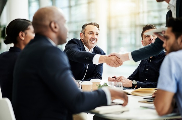 Six people gathered around a conference table while two of them shake hands.