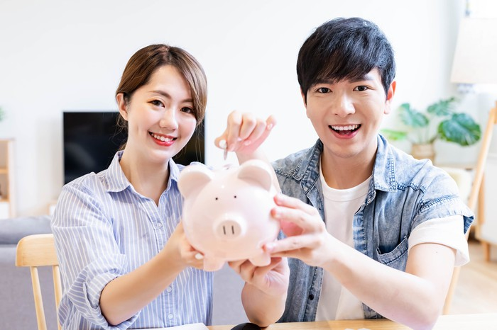 Two people putting money into a piggy bank.
