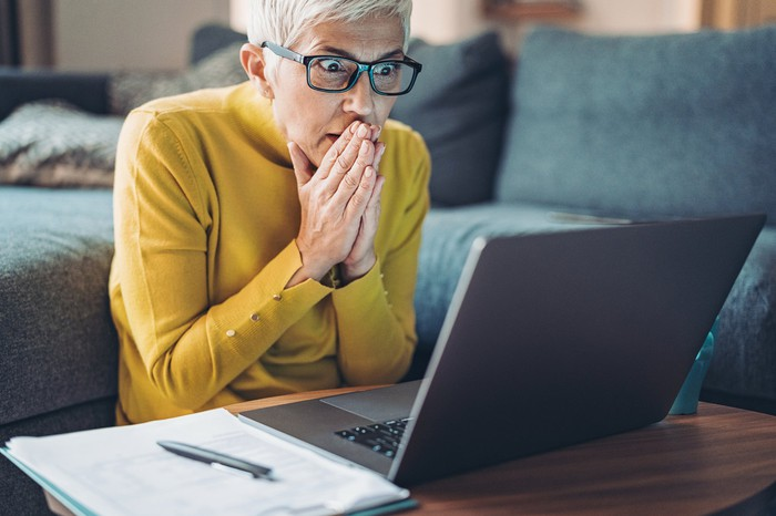 Mature person looking at laptop screen in shock