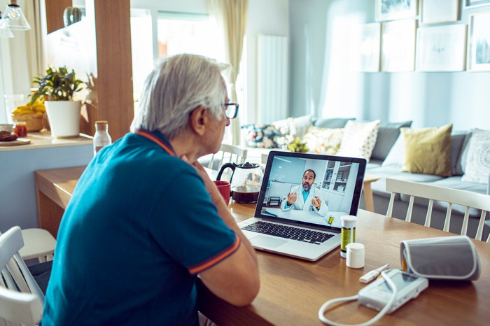 Elderly patient consulting with a doctor online.