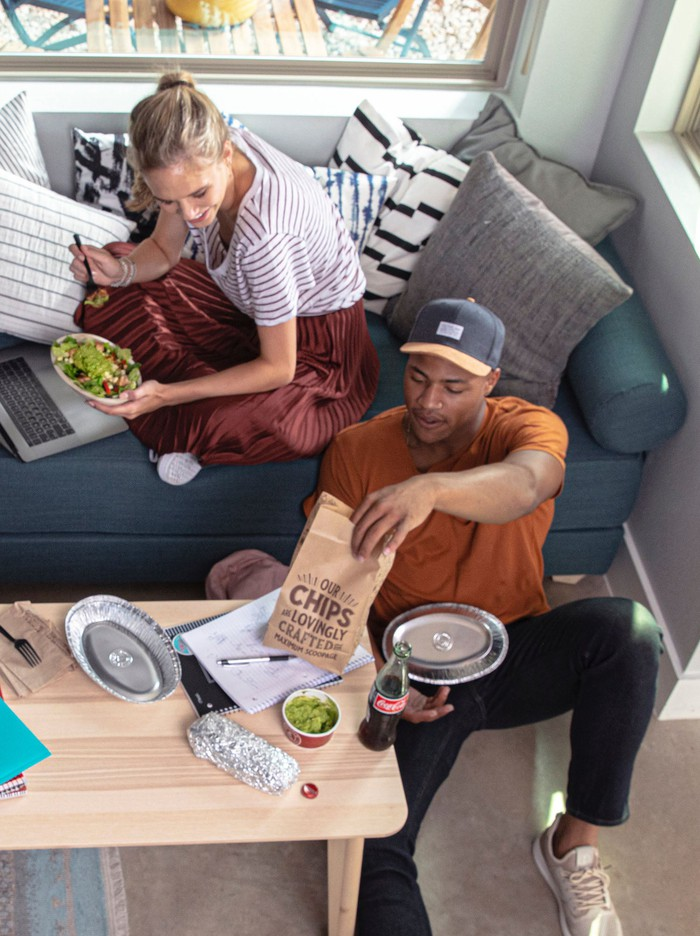 two people sitting by the couch eating Chipotle