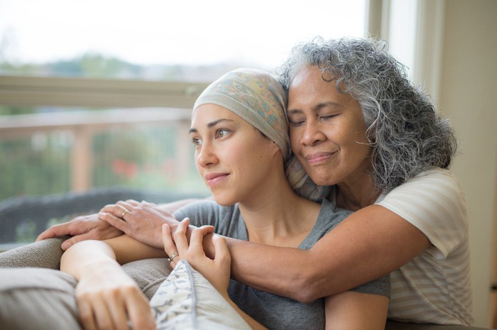 An older person hugging a younger cancer patient from behind as they sit and look out a window.