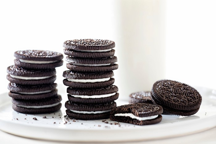 Oreo style sandwich cookies stacked on a white platter, with a glass of milk in the background.