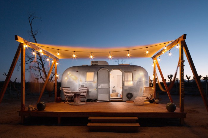 A decorated camper-trailer on a wooden deck covered by a lit canopy.