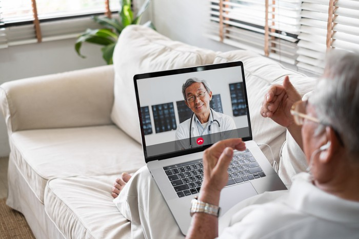 A senior citizen using a laptop to have a virtual consultation with a doctor.