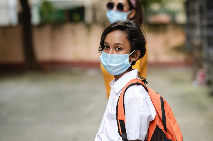 A young person wearing a backpack and a surgical mask.
