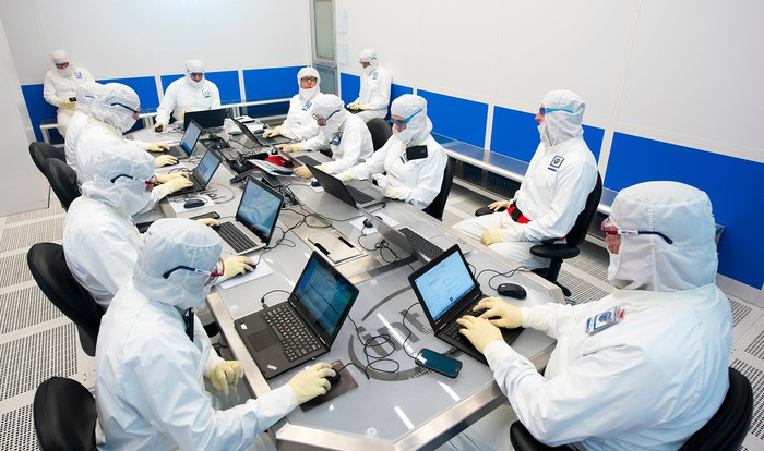 12 Intel engineers wearing cleanroom suits in a fab.