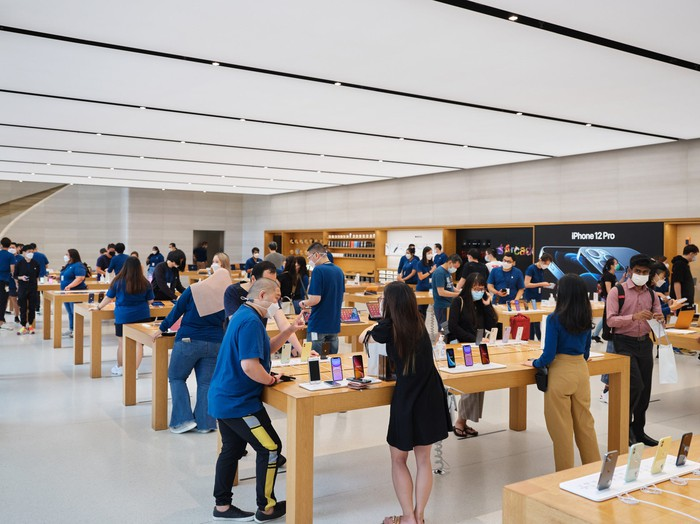 Customers browsing inside an Apple retail store.
