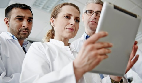 three scientists look at tablet while worried