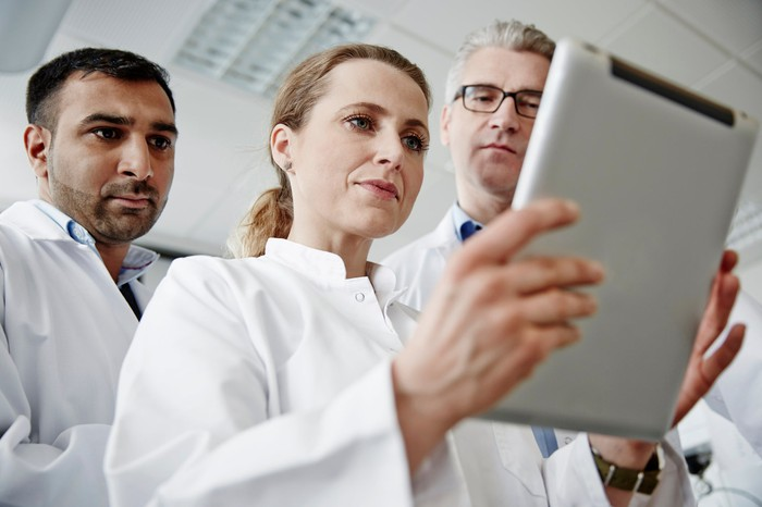 Three scientists look worried as they consult a data readout on a tablet.