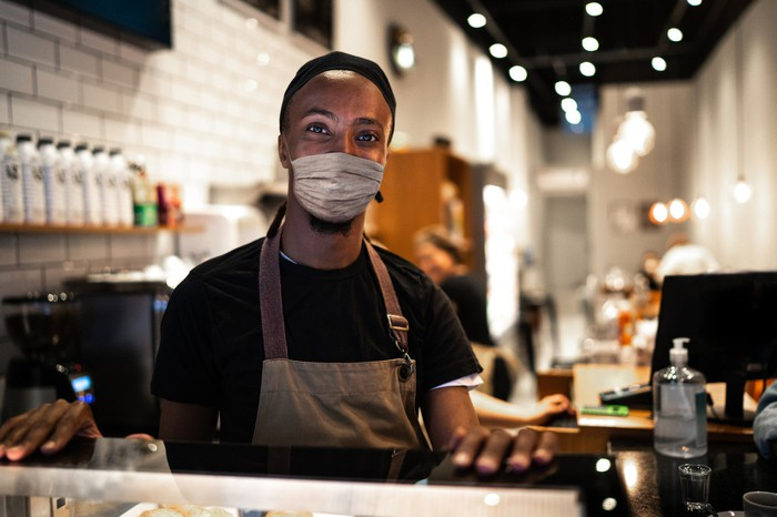 A masked barista stands behind the counter in a coffee shop.