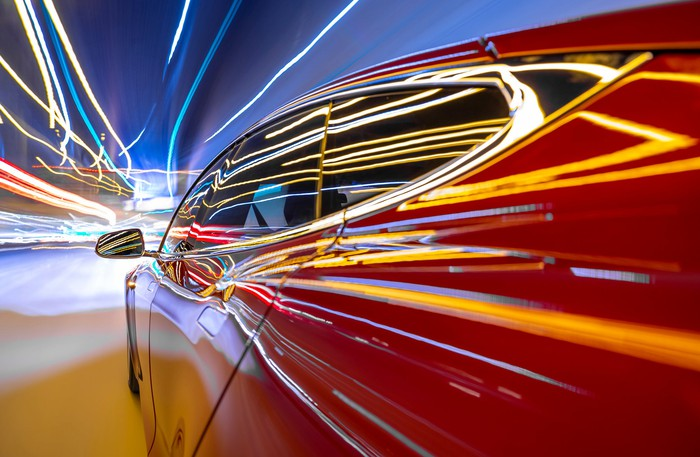 Lights streak down a red electric car racing down the highway