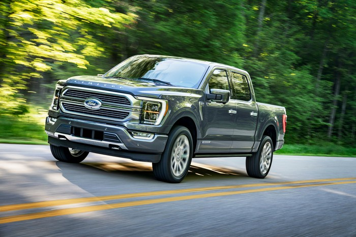 A silver 2021 Ford F-150 pickup truck driving on a road with trees in the background.