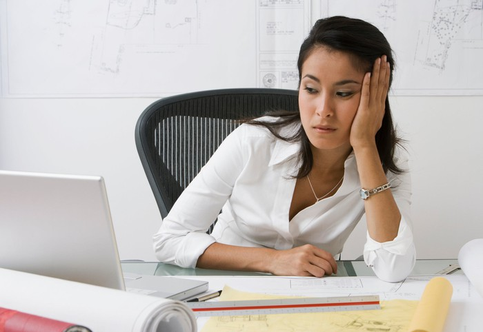 Person at desk looking at laptop suspiciously