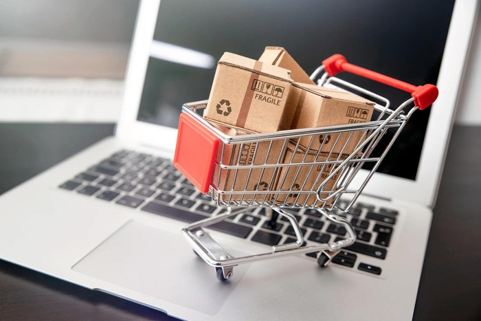 Tiny shopping cart filled with boxes on top of a keyboard.