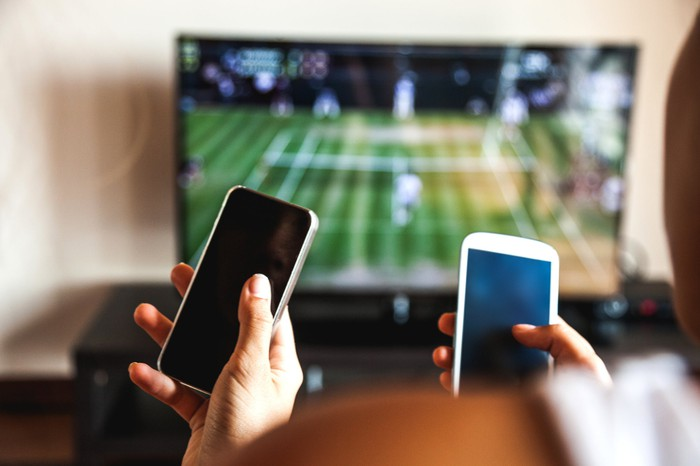 Two people look at cell phones while watching a tennis match on TV.