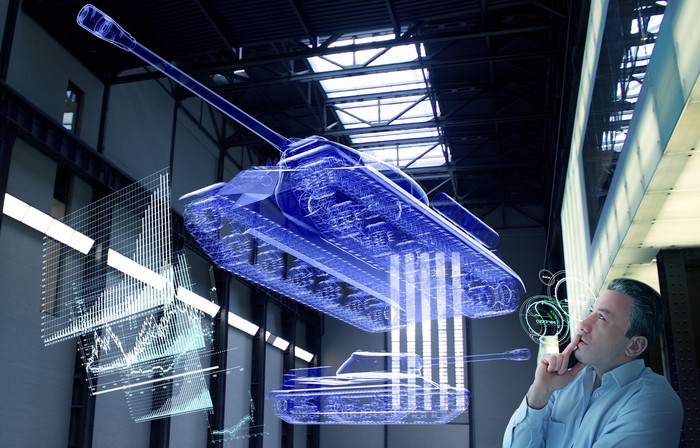 Engineer examining holographic designs of a futuristic tank