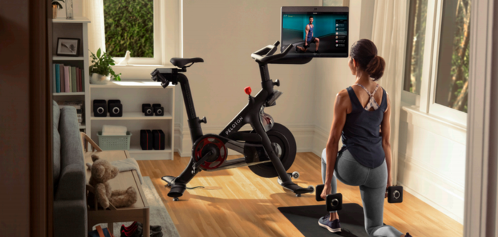 Woman using weights while watching an instructor on a Peloton bike's screen.
