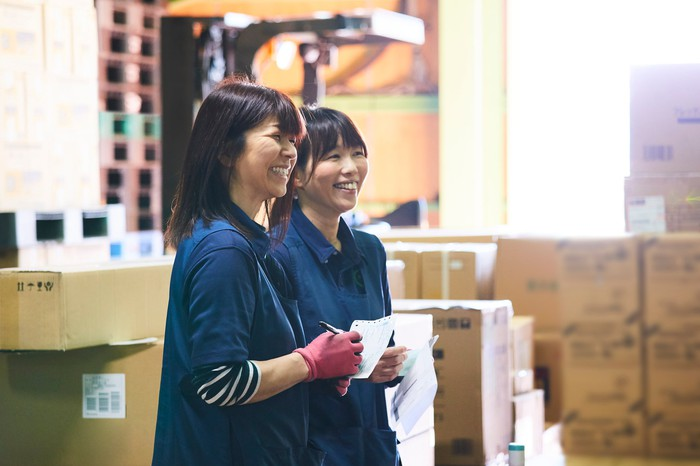 Two workers smiling in a warehouse.