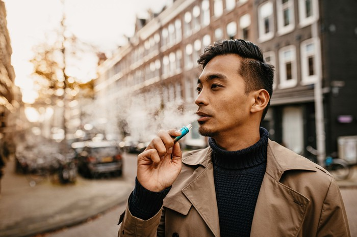Person looking to the left with a trench coat holding a blue electronic cigarette to their lips.