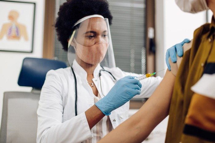 A doctor wearing a mask and face shield vaccinates a patient.