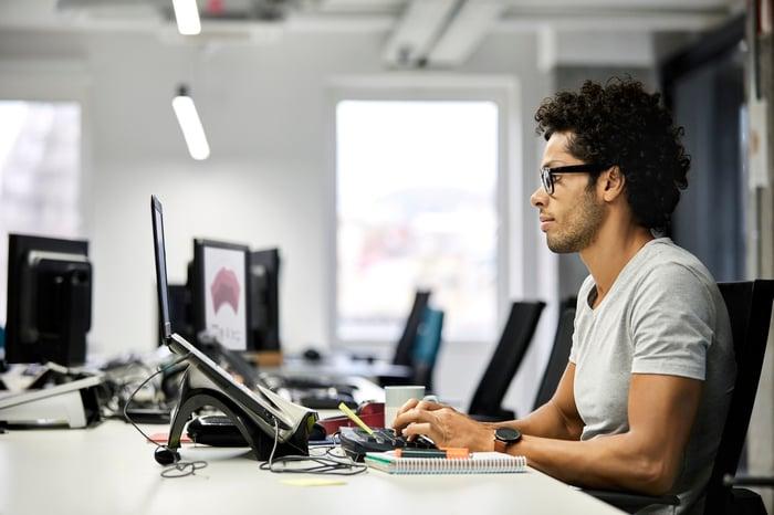 A tech worker uses a desktop computer at an office.