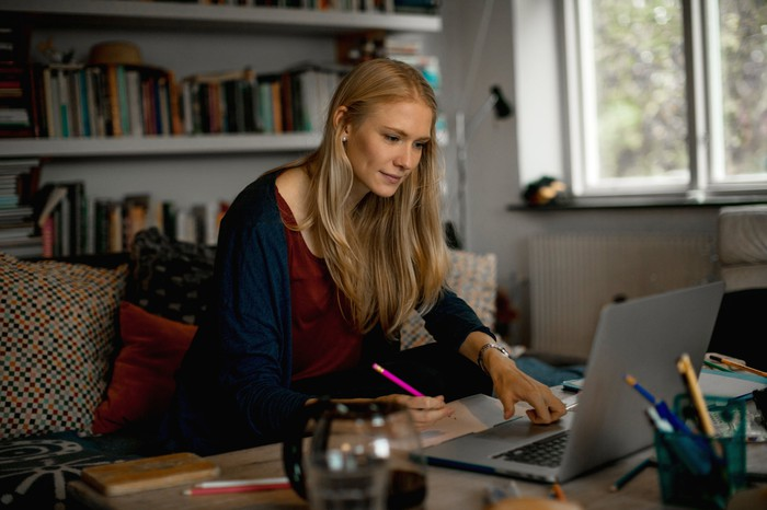 Woman with pencil looking at computer