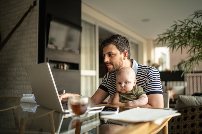 A dad holding a baby and looking at his laptop.