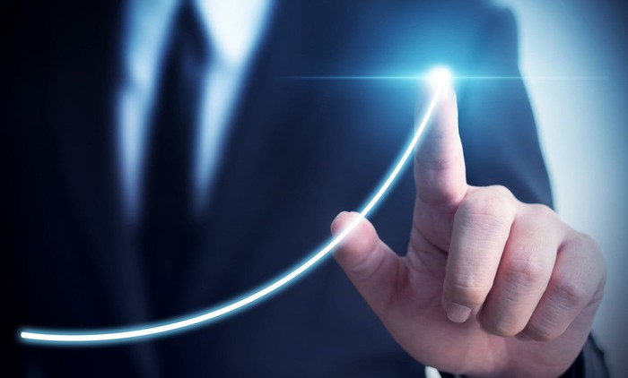 Person pointing finger at an upward curve that's glowing.