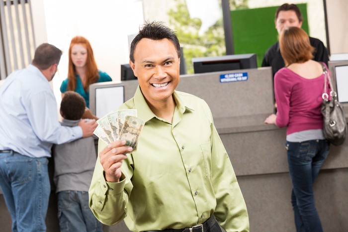 A happy person holding money at a bank branch.